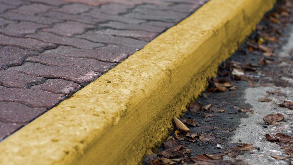 Onde o meio-fio for pintado de amarelo NÃO pode estacionar?